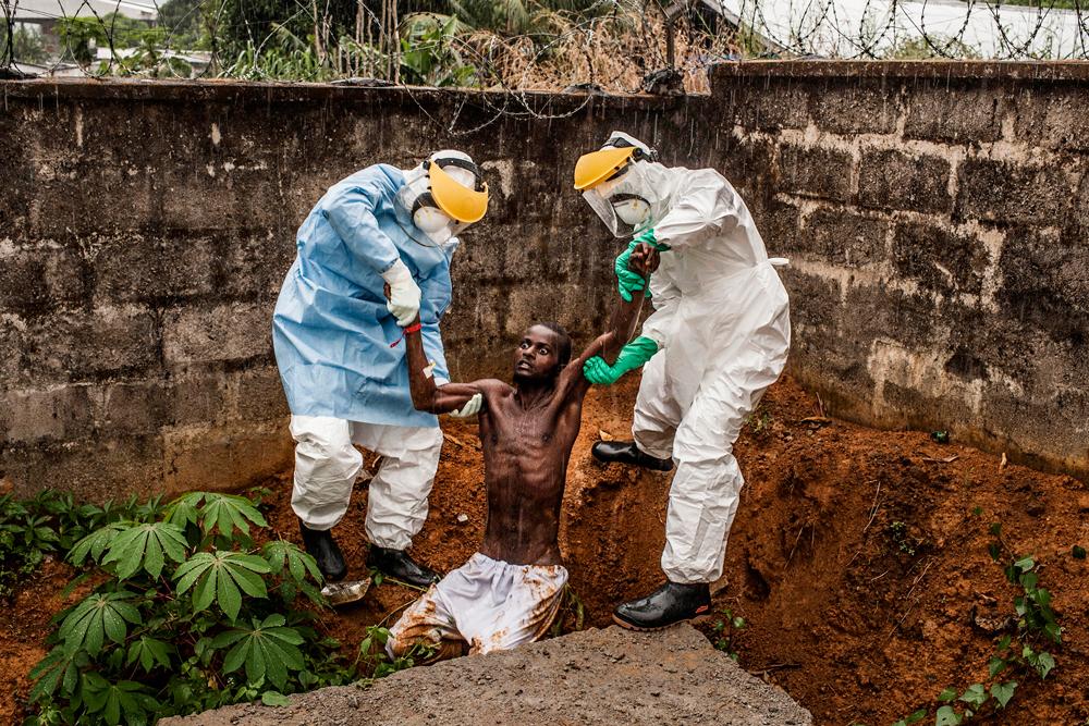 Operatori medici portano un uomo malato di ebola in isolamento a Freetown, in Sierra Leone
