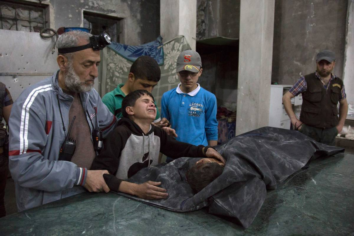 A Syrian boy is comforted as he cries next to the body of a relative who died in a reported airstrike on April 27, 2016 in the rebel-held neighbourhood of al-Soukour in the northern city of Aleppo. / AFP / KARAM AL-MASRI (Photo credit should read KARAM AL-MASRI
